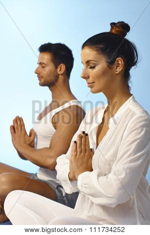 Young couple meditating eyes closed in peace.