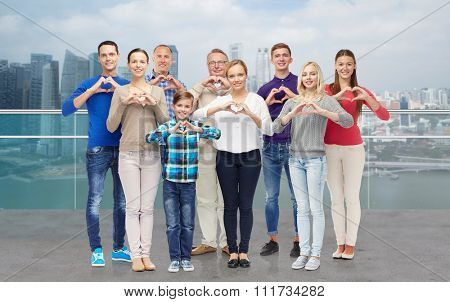 gesture, family, generation and people concept - group of smiling men, women and boy showing heart shape hand sign over singapore city waterside background