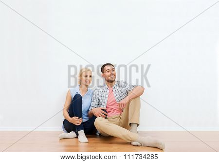 home, people, repair, moving and real estate concept - happy couple of man and woman sitting on floor and dreaming at new place
