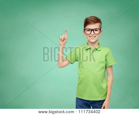 childhood, vision, school, education and people concept - happy smiling boy in green polo t-shirt in eyeglasses pointing finger up over green school chalk board background