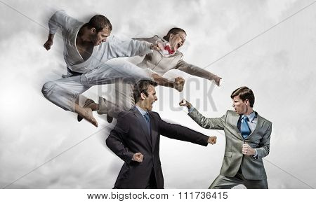 Young determined karate man fighting with team of businesspeople