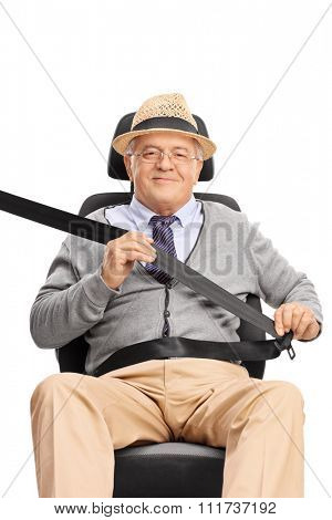 Senior gentleman sitting on the passenger seat fastened with a seatbelt and looking at the camera isolated on white background