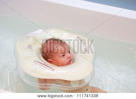 Newborn baby swimming with neck swim ring