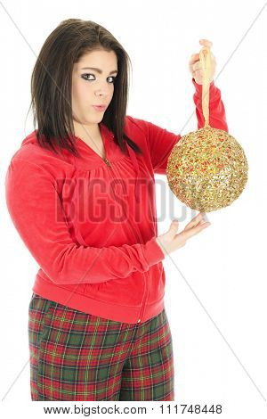 A beautiful teen girl wearing pajamas showing the viewer her favorite giant Christmas bulb. On a white background.
