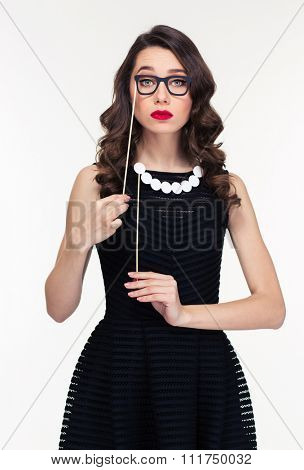 Amusing curly young woman in retro style posing with fake beads and glasses booth isolated over white background