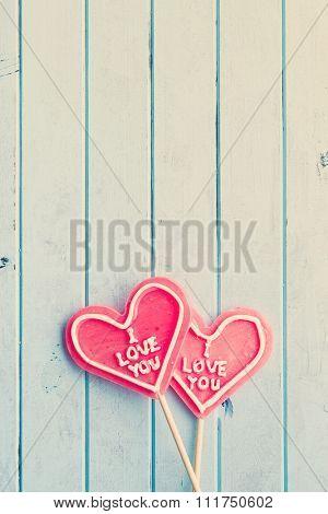 lollipops shaped heart on wooden background