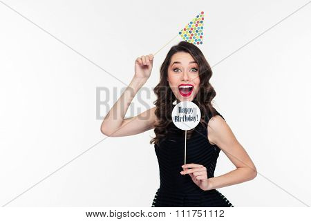 Smiling joyful pretty curly young woman with bright makeup in retro style posing with birthday props isolated over white background