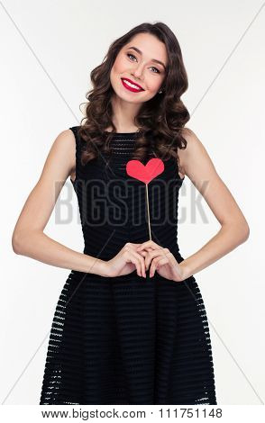 Attractive smiling pleased curly young woman in retro style standing with heart props over white background
