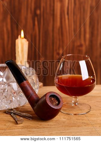 A Glass Of Cognac And Smoking Pipe