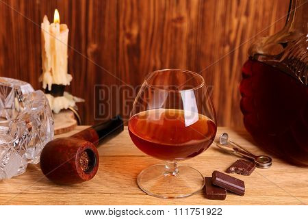 A Glass Of Cognac, Chocolate And Smoking Pipe