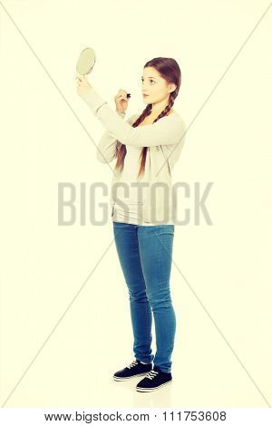 Young woman applying lipstick looking at mirror.
