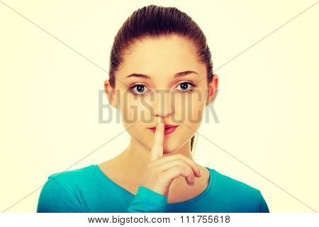 Beautiful teen woman with hush gesture.