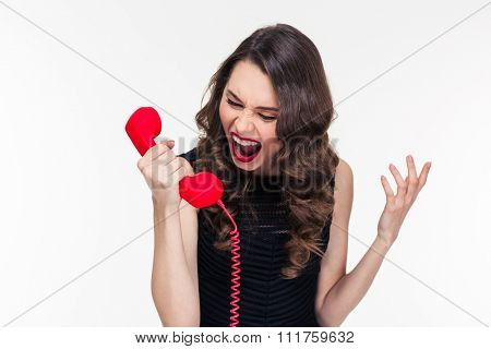 Crazy raged retro styled curly young female shouting in red telephone receiver over white background