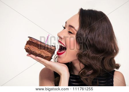 Positive beautiful young woman in retro style biting piece of chocolate birthday cake with candle over white background