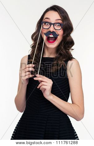 Funny cheerful young woman with bright makeup in retro style having fun using glasses and moustache props over white background