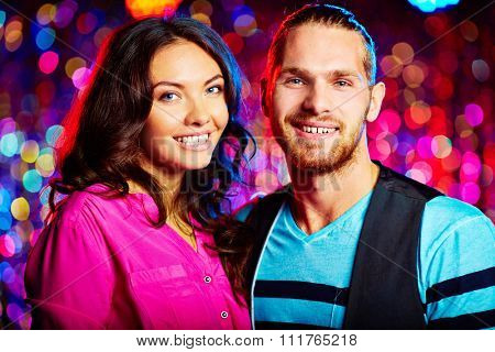 Amorous couple looking at camera at party
