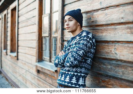 Handsome Young Man In A White Knit Sweater And Cap Near A Wooden House.
