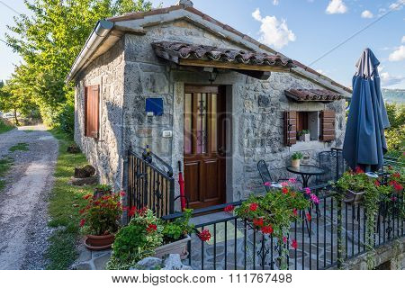 Small Stone House With A Metal Fence
