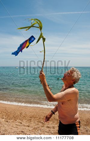 Elderly Man Is Playing At The Beach