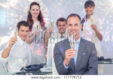 Successful business coworkers toasting with Champagne against colourful fireworks exploding on black background