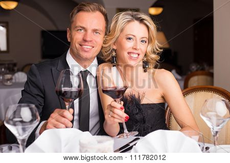 Happy couple with glass of wine in their hands