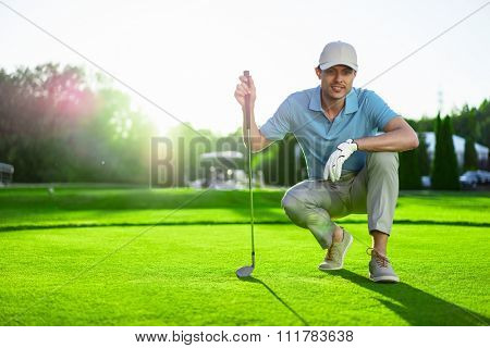Young golfer with club on a lawn