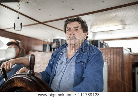 BEAUFORT, SOUTH CAROLINA-OCTOBER 16, 2015: Unidentified fishing captain drives a fishing vessel off the coast of South Carolina.