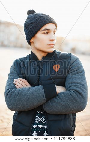 Stylish Young Man In Knitted Hat, Sweater And Jacket On The Background Of The City On A Sunny Day