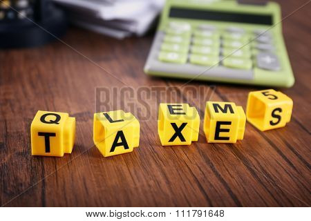 Alphabet TAXES and calculator on wooden table