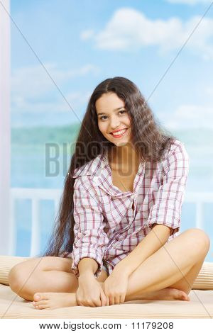 Young Smiling Woman Sitting On Bad