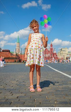 Portrait in full growth - the young girl with pinwheel standing on Red Square