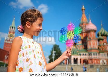 Young happy girl with pinwheel stands on Red Square looks aside