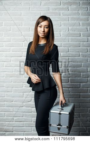 Young Beautiful Girl In A Black Dress Holding A Stylish Aluminum Case Against A White Brick Wall