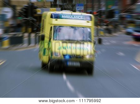 Emergency ambulance travels through city street. Zoom effect applied for dramatic effect.
