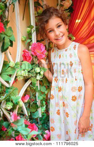 Goodly little girl holding red flower. Smile, joy, gladness.