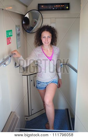 Young woman passanger rising stairs inside moving train, text on wall: exit, temperature 24 C