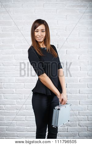 Young Business Woman Holding An Aluminum Case On A Background Of White Brick Wall
