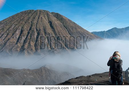 Woman taking a picture of the Mountain with fog and mist