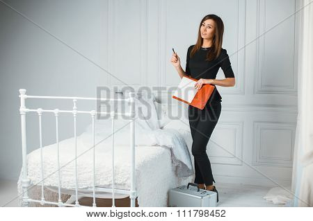 Beautiful Girl Wedding Coordinator Near The Bed And Holding A Notebook With A Pen.