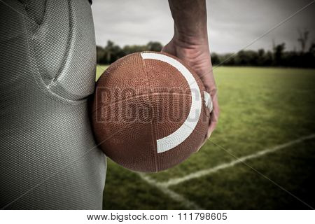 American football player holding ball against empty rugby pitch