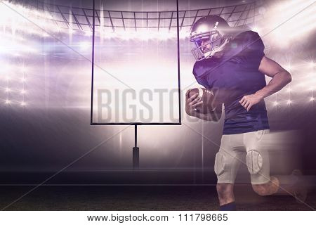American football player holding ball in mid-air against american football arena