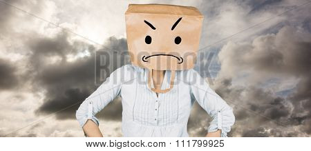 Woman with hands on hip and covering head with brown paper bag against blue sky with white clouds
