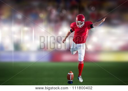 American football player kicking football against sports arena