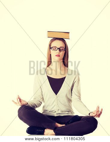 Woman sitting cross-legged holding book on head.