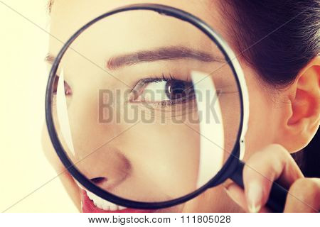 Woman looking through magnifying glass.