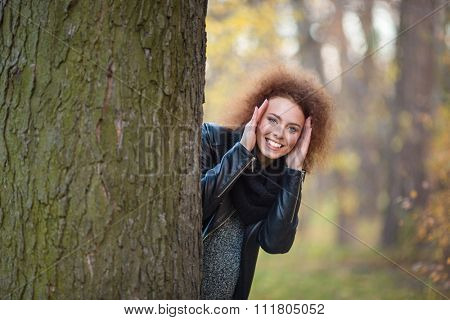 Portrait of a smiling woman with curly hair peeking out from behind a tree in autumn park
