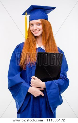 Portrait of pretty redhead cheerful graduated positive girl in blue gown and graduation cap holding clipboard
