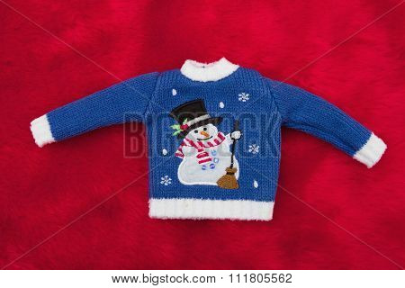 White And Blue Snowman Christmas Sweater On Red Plush Fur