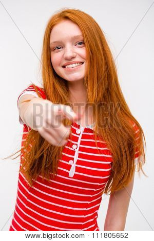 Beautiful cheerful joyful redhead teenager red striped t-shirt pointing at the camera on a white isolated background