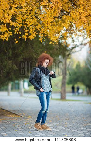 Full length portrait of a young woman waiting somebody and looking on wrist watch outdoors in park